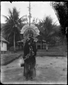 back view of man holding a drum, wearing a large elaborate feather headdress (oa oa ?) standing on dancing ground ?