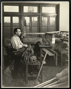 Blind man fastening straw on broom handles at the Bourne Memorial Building, New York, 1921 (silver gelatin print)