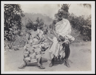 2 male elders, both seated and wearing beards and bodycloths and sandals