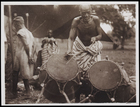 1 Male in Striped Body Cloth Playing 2 Drums With 2 Onlookers