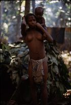 A young woman, Goma, carrying a child (her cousin, Etu) on her shoulders.