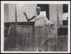 1 male in a body cloth holding a woven mat