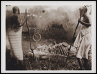 2 females supervising the firing of pots