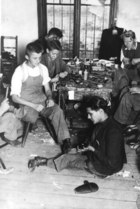 Young men working in a workshop of shoes making (some of them are disabled, one-legged person) 20's