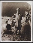 1 male standing in front of the body of a drum under a shelter with upturned drum body upside down
