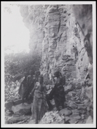 2 females in the foreground, 3 others behind walking beside a rockface