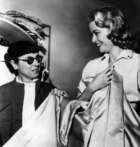 Grace Kelly smiles in agreement with Edith Head, costume designer for Paramount Studios as she approves the coat she will wear at the Academy Award presentations