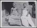 2 females in decorative body cloths, bracelets and 1 with a necklace, seated in front of a mud house